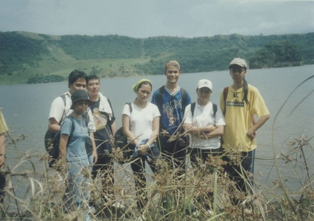 group of people posing with the Tabaro Main Crater of Taal Volcano in the background