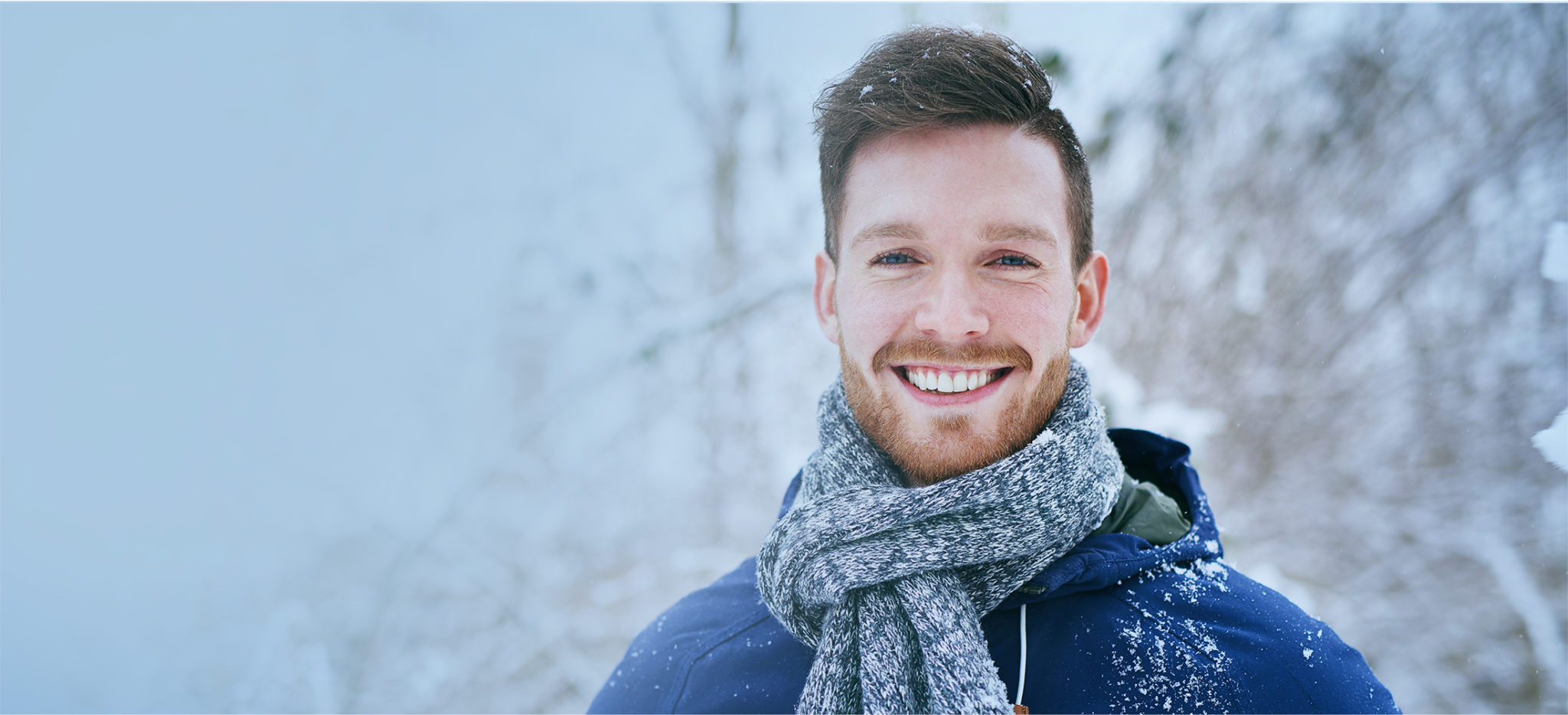 Smiling Man with a scarf in a snowfall