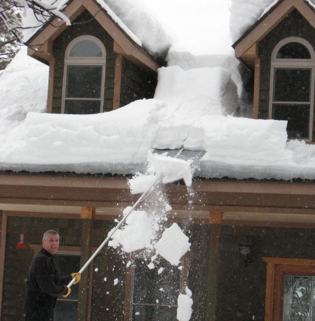 Snow covered roof being cleared off by a Roof Razor