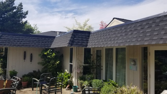 Composition shingles installed over the sloped portions of a roof in Salem, Oregon.