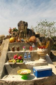"""Neben der offiziellen Widmung für den Hindu-Gott Shiva, beherbergt der Tempelkomplex auch etliche andere Geister und wird für lokale Kulte genutzt. Der hier abgebildete Schrein huldigt einen Helden, der sich im Kampf mit den Thais aufgeopfert hat und nach einer feierlichen Zeremonie von den Klippen gesprungen ist. Das """"Opfer"""" für einen höheren Zweck – in jeder erdenkbaren Form und Größe – ist ritualisierter Bestandteil der Gesellschaft."""