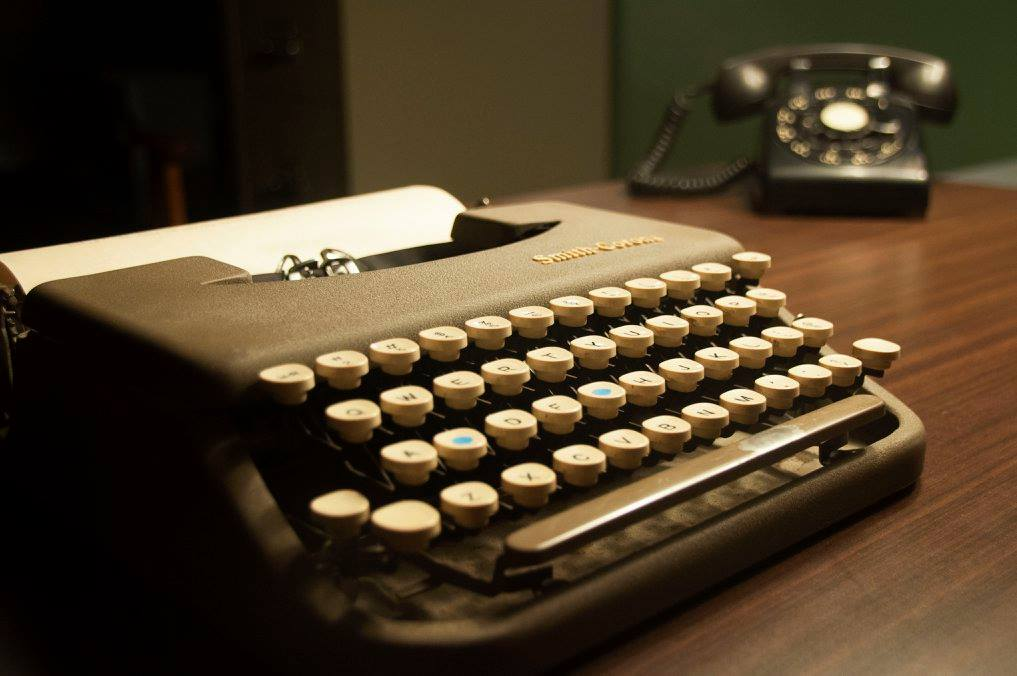 An old typewriter sits in the foreground. An old rotary phone sits out of focus in the background.