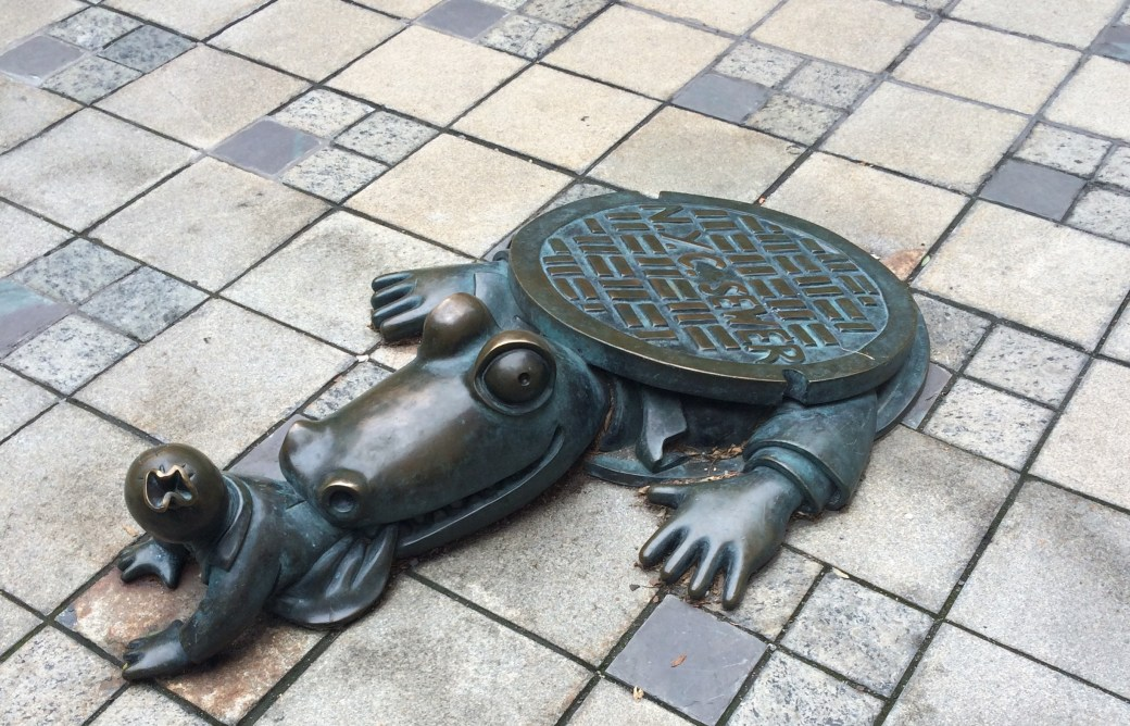 A bronze sculpture built into a sidewalk of an alligator wearing a suit emerging from a NYC manhole and eating a person. It's strangely cute.