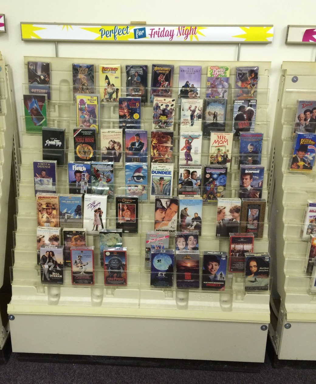 A video rental shelf containing a variety of 1980s classics movies, and some that aren't quite so classic.