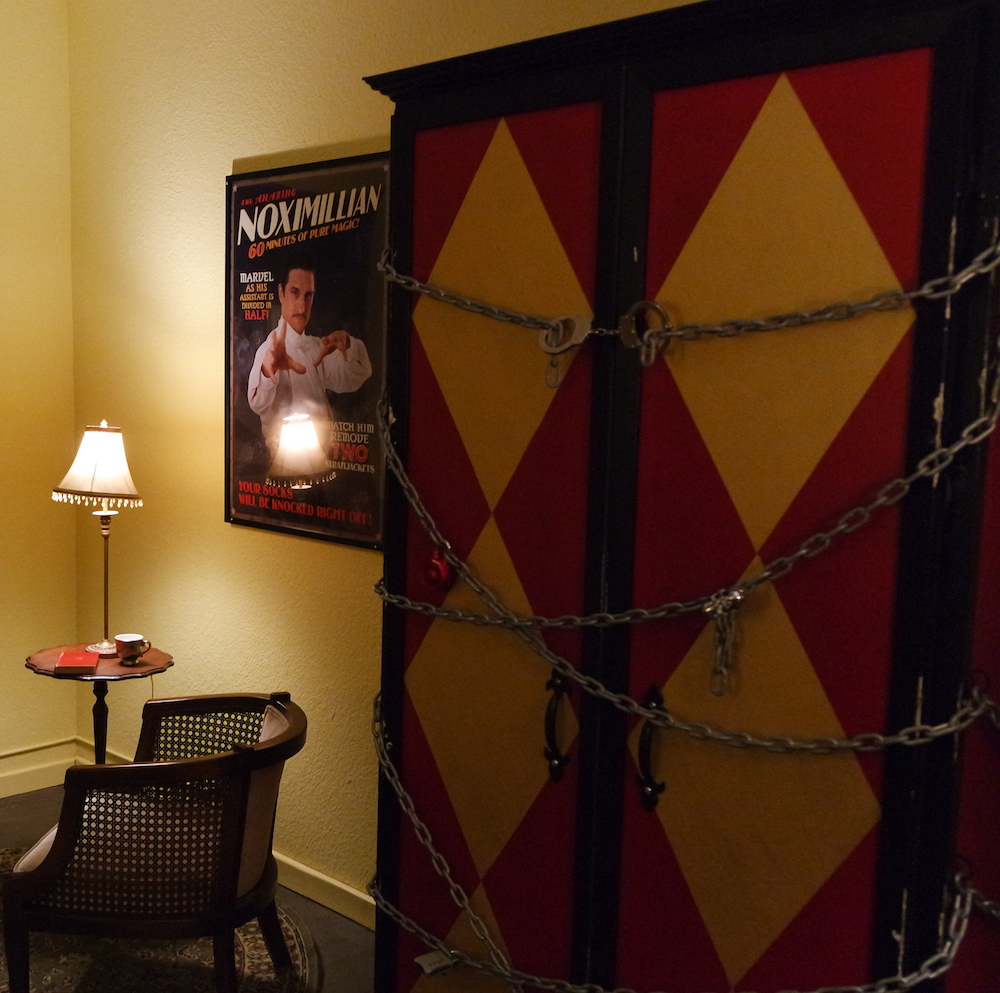 Interior of the Vanishing Act. Depicts massive a red and yellow box chained and locked shut with multiple locks. A poster of Noximillian hangs on the wall beside the box.