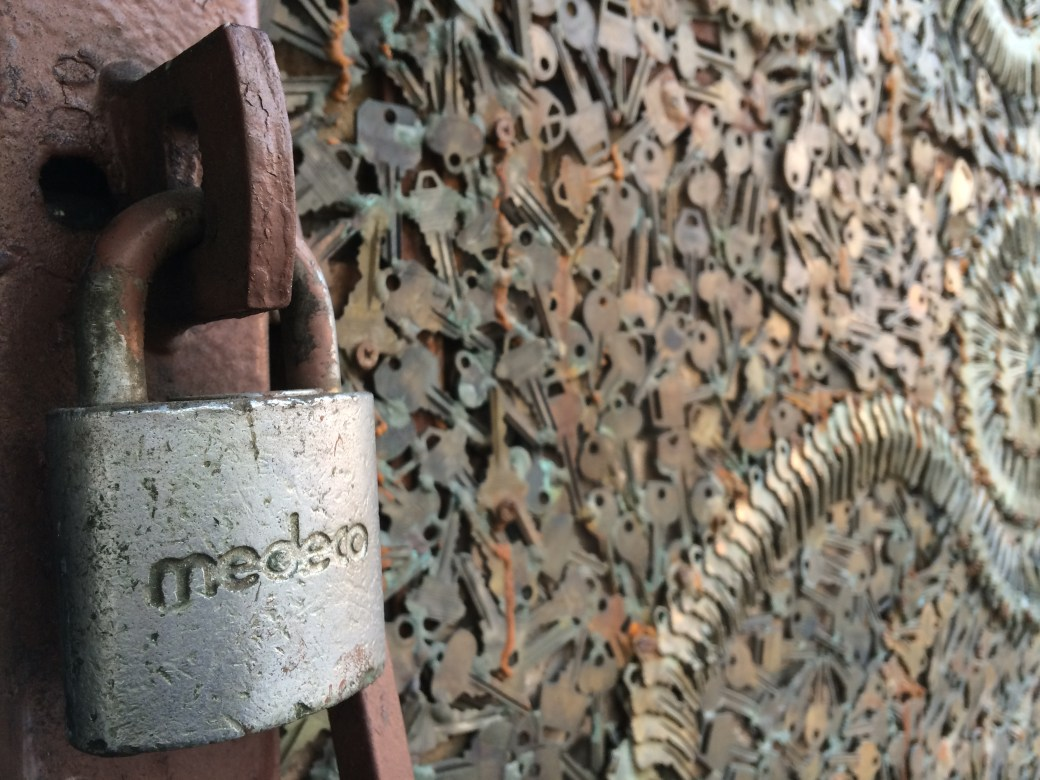 Photo of a medeco padlock afixed to a rusty hasp. In the background is a mosaic made of keys.