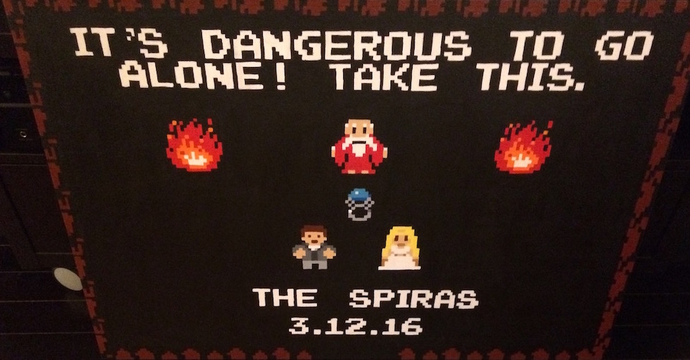 "8 bit painting inspired by Zelda - It says, ""It's dangerous to go it alone! Take This. The Spiras 3-12-16."" It depicts an old man in a fire-lit cave giving a ring to a couple dressed for a wedding."