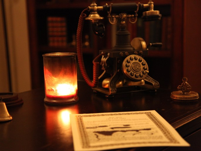 Image of a old-looking telephone and an ink-smeared letter, all lit by a candle.