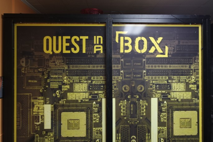 """An odd box that nearly reaches the ceiling. It says, """"Quest in a Box"""" on its side."""