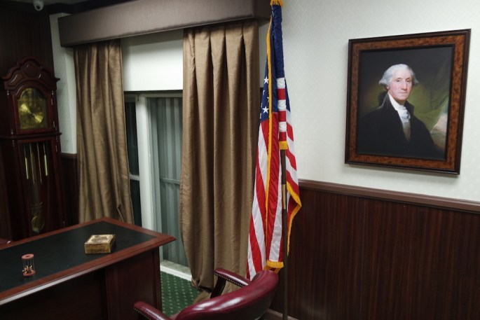 An escape room designed to look like a senator's office, complete with George Washington portrait, American flag, desk, leaver chairs, and grandfather clock.