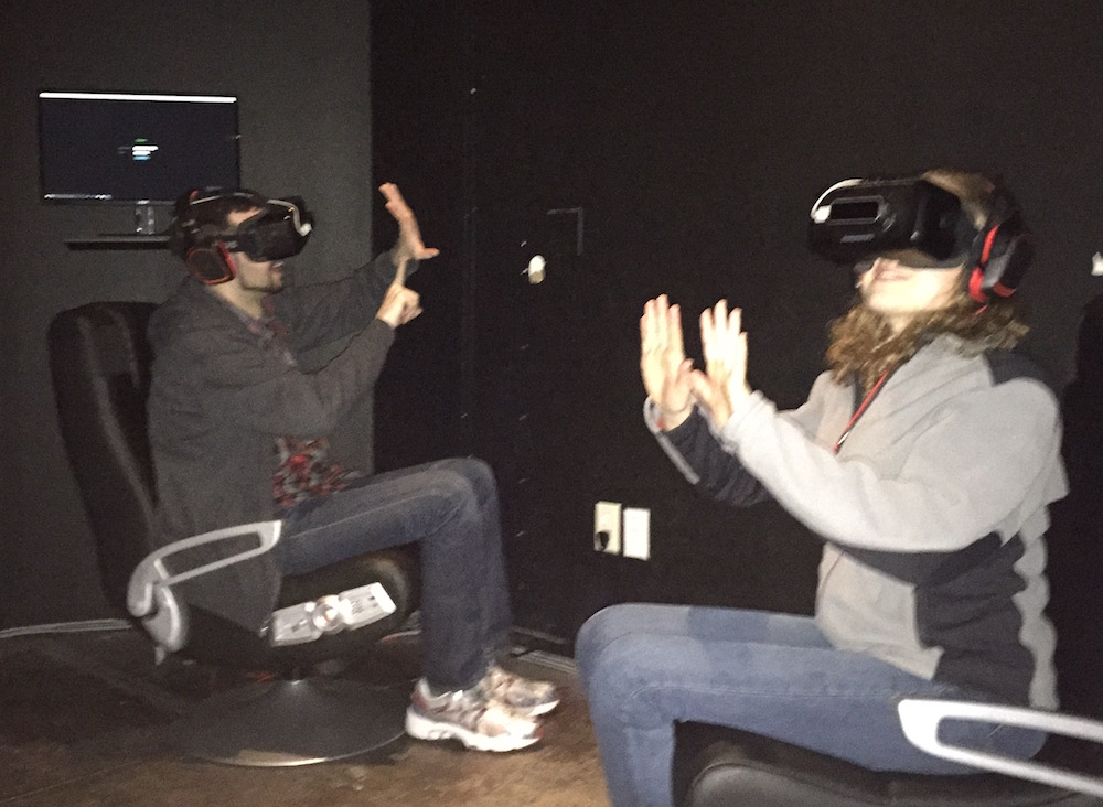 Lisa and David in chairs wearing VR masks and headsets, gesturing as they play.