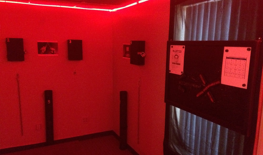 Interior of the game, the room is lit with red, with sparse design, and black locked boxes hanging from the walls.