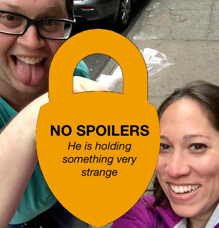 A selfie of two people holding something. The object they are holding is obscured by a sign reading,