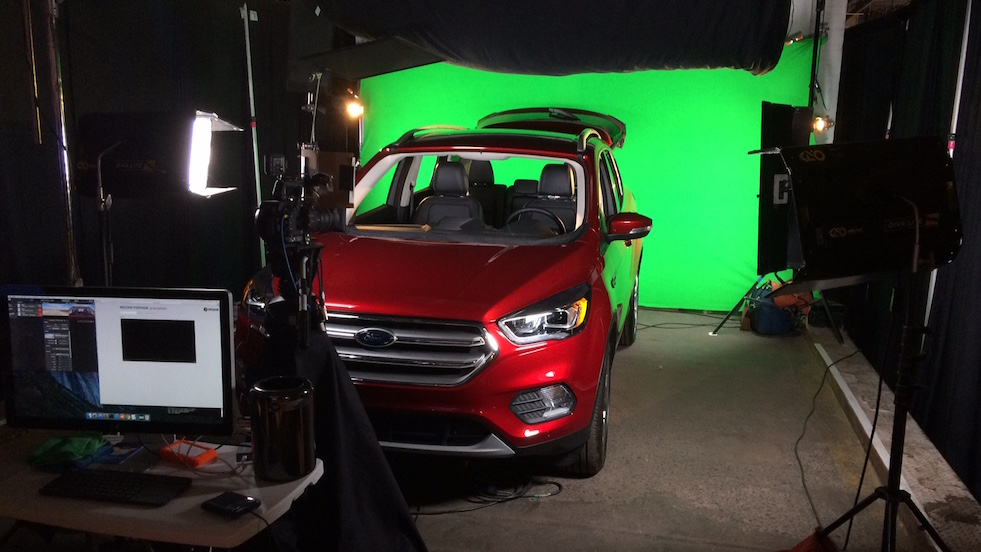A Ford Escape with a green screen in the background. The car is surrounded by cinematic lighting.