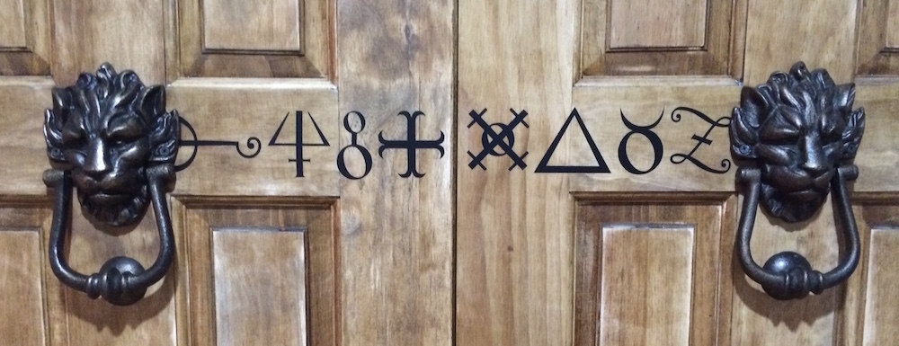 Double wood doors with runs painted on them, beset by a pair of black lion door knockers.