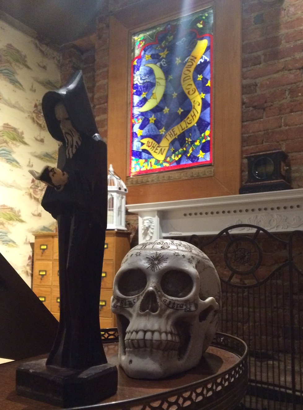 In-game photo of a wizard statue, an intricately engraved human skull, and a stainglass window in the background.