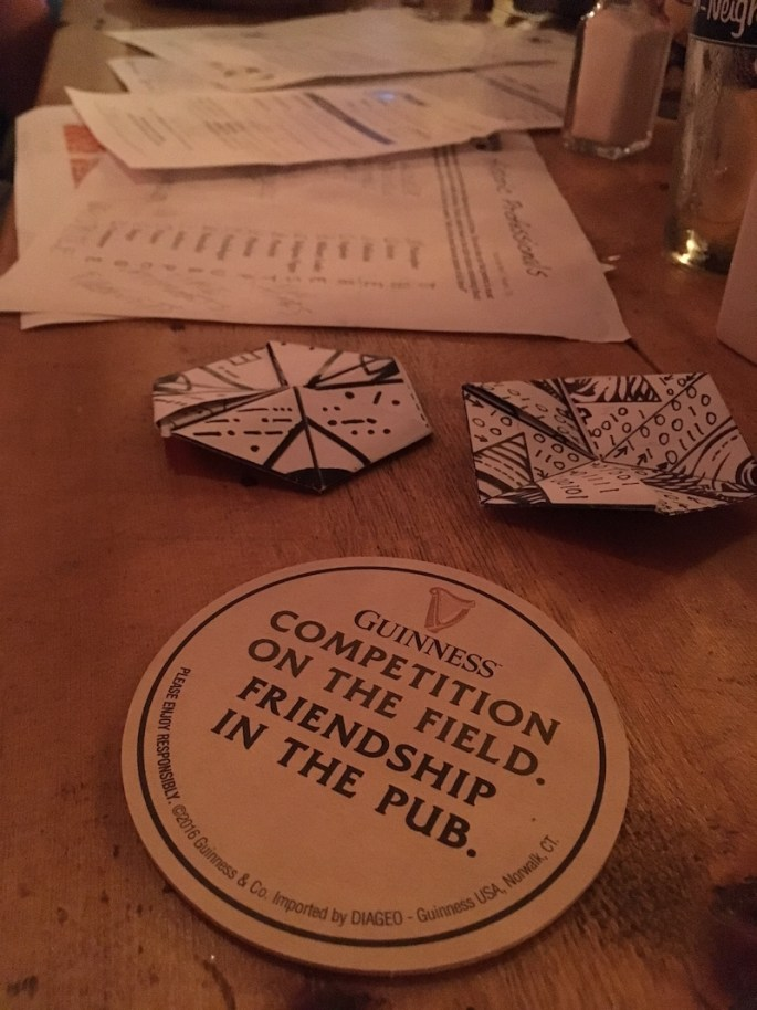 "A coaster that reads, ""Guiness: Competiton on the field. Friendship in the pub."" rests in front of a variety of paper puzzles."