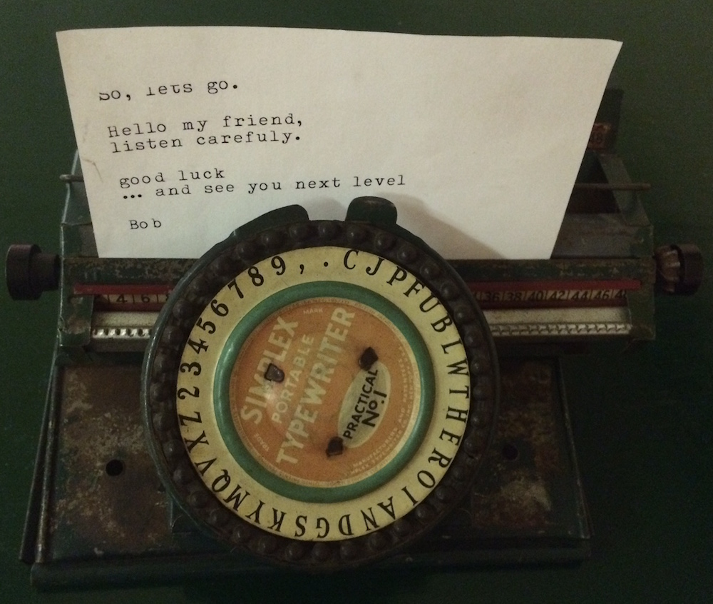 """An old portable typewriter with a typed letter in it. It reads, """"So, let's go. Hello my friend, listen carefuly. good luck ... and see you next level Bob"""""""