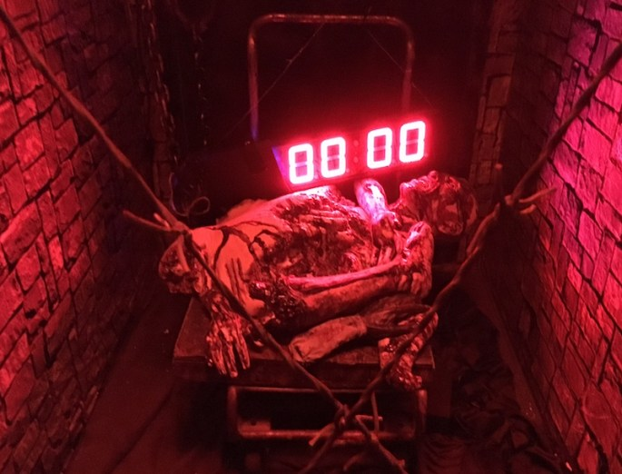 In-game: A red digital countdown clock illuminates a dead body