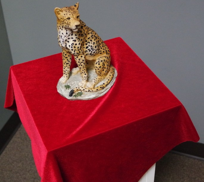A cheetah statue on a red clothed pedastal.