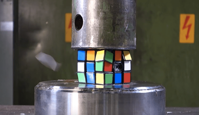 A hydraulic press starting to crush a Rubik's Cube.