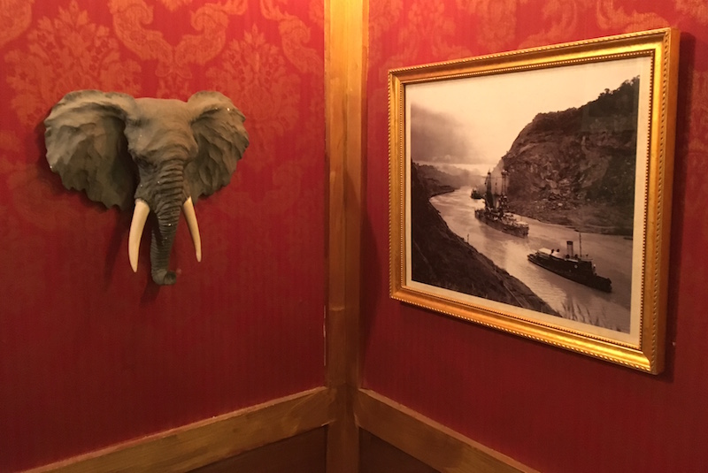 In-game image. A corner with red wallpaper and gold trim. A photo of the Panama Canal hangs on the wall beside an elephant's head.