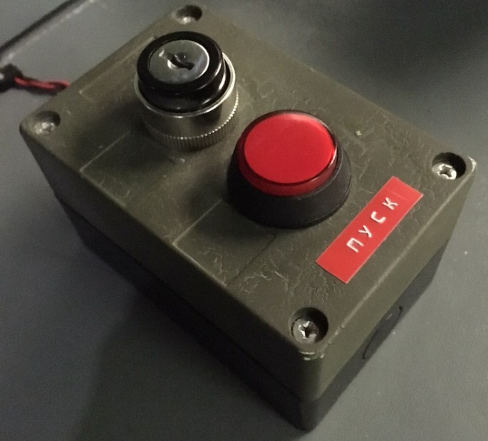 Close up of a big red button with a keyway next to it. There is a label with Russian written on it.