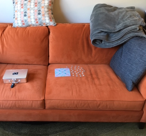 A scrabble-based puzzle spread out on an orange couch. A locked box sits beside it.