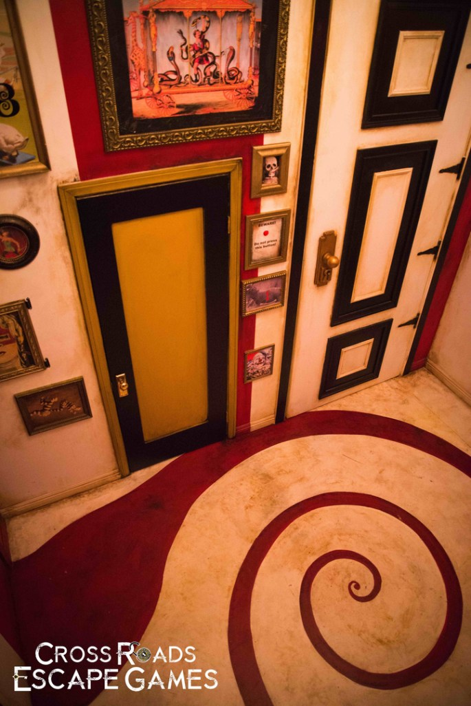 In-game, a colorful room with large and small doors, images all over the wall,s and a spiral pattern on the floor.