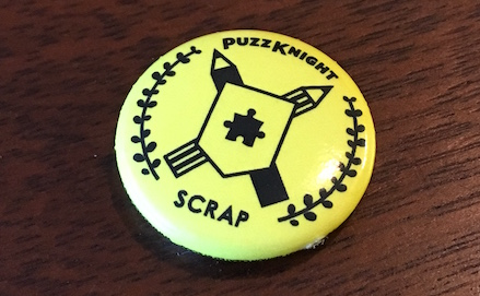 A small yellow pin with a puzzle coat of arms. The pin reads,