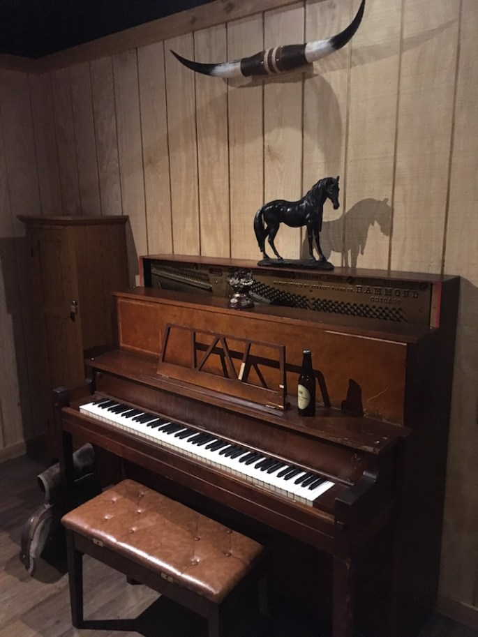 In-game. An old piano with a beer and horse statue resting on it.