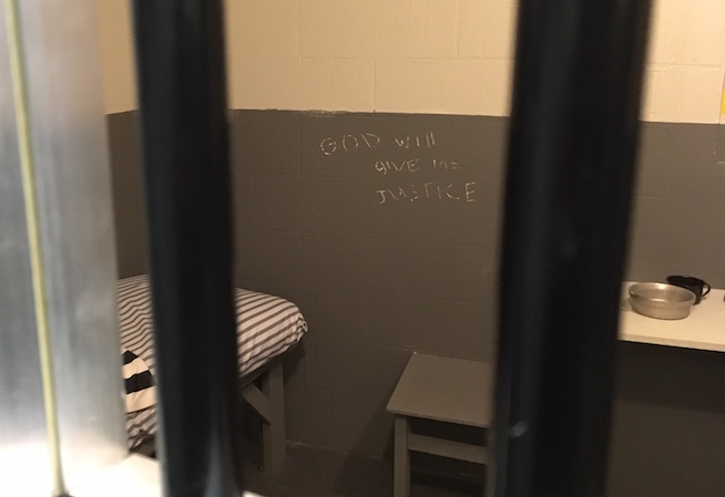 """In-game image shoth through the bars of a jail cell. A small kot and table rest in the room.Scratched into the cell's grey walls are the words, """"God will give me justice."""""""