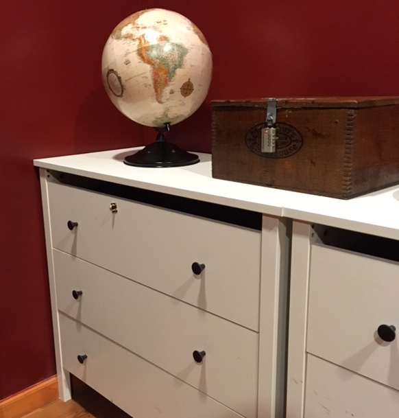 In-game a photo of a mundane set with a pair of white dressers. A globe and a lockbox rest atop the dressers.