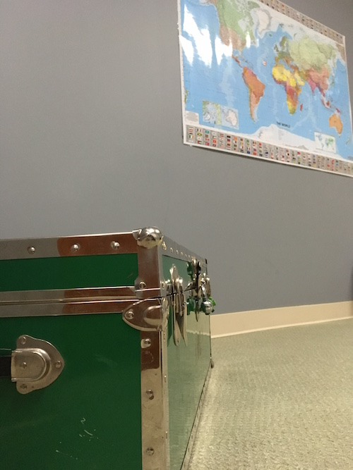 A trunk sits on the floor with a laminated world map in the background. The room looks bland and boring.