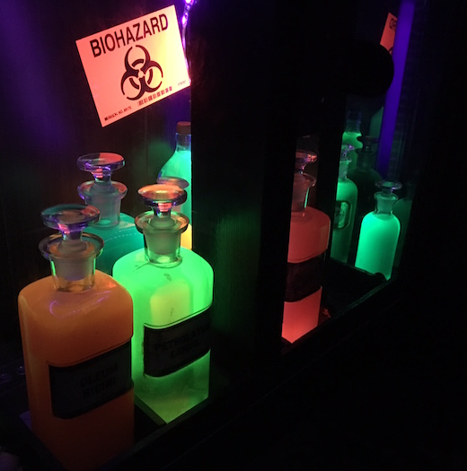 "In-game: A cabinet in a dark room illuminated by UV light with fluorescent bottles. An orange sign reads, ""Biohazard."""