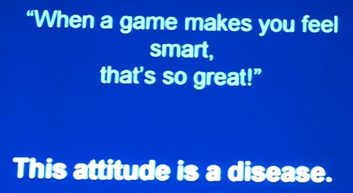 """Screenshot of video, blue background with white writing reads, """"'When a game makes you feel smart, that's so great!' This attitude is a disease."""""""