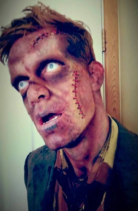 Detailed zombie makeup on a male actor. He looks very undead.