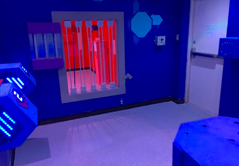 In-game: The Blue Room features a variety of interactions. Through a barred window, the Red Room is visible.
