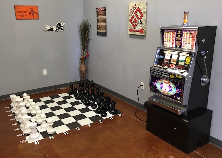 In game: A one armed bandit slot machine rests in the foreground. A massive chess board is built into the floor.