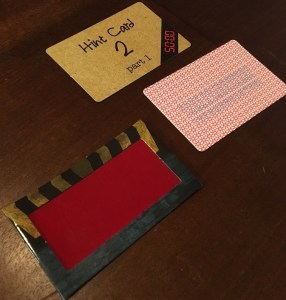 The hint decoder, the back of one hint card, and the blurring front of another.
