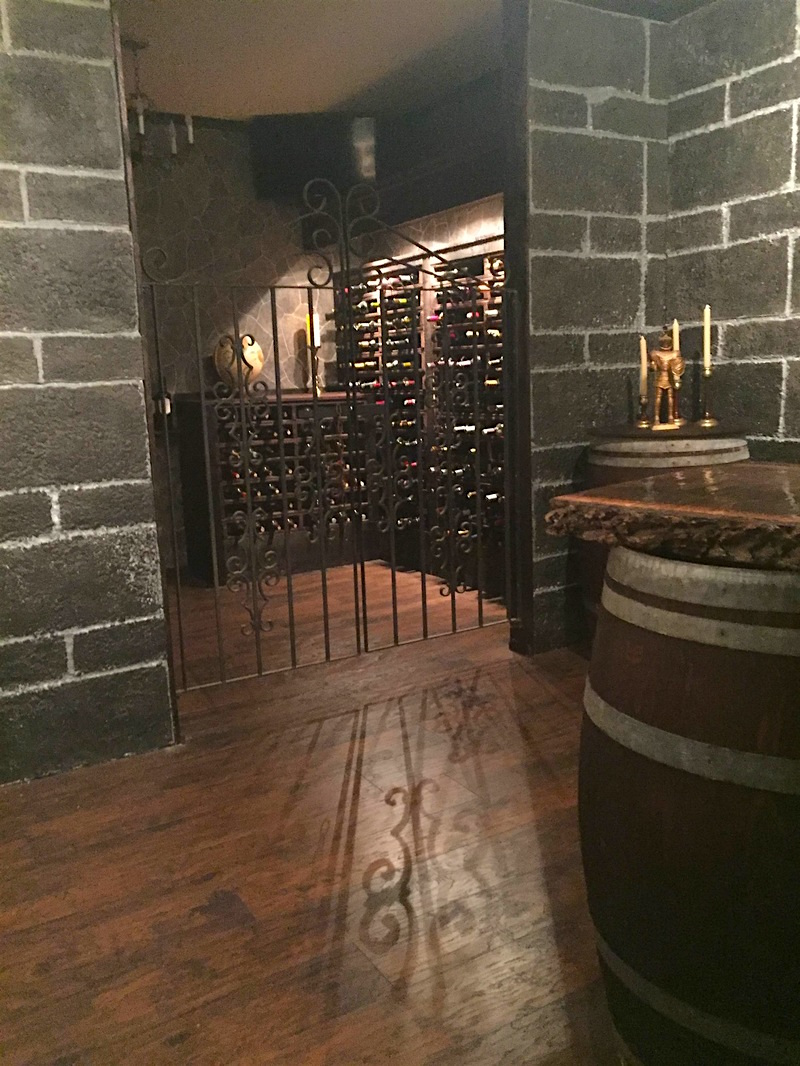 In-game: A wine cellar with stone walls, barrels, and large racks of wine behind an iron gate.