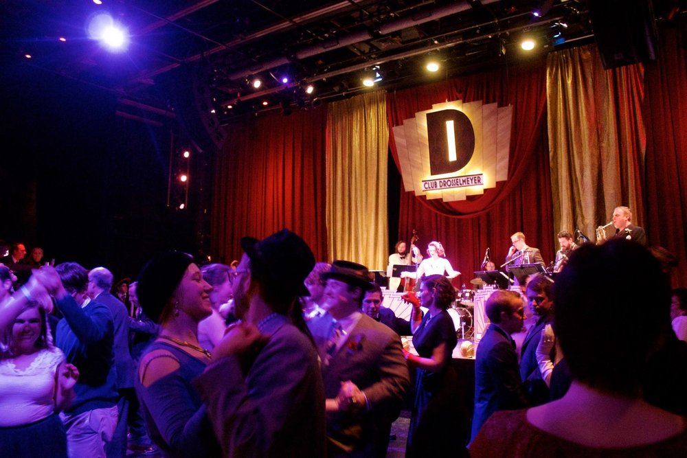 In-game image of a the ornate Club Drosselmeyer stage witha swing band and a floor full of people dancing.