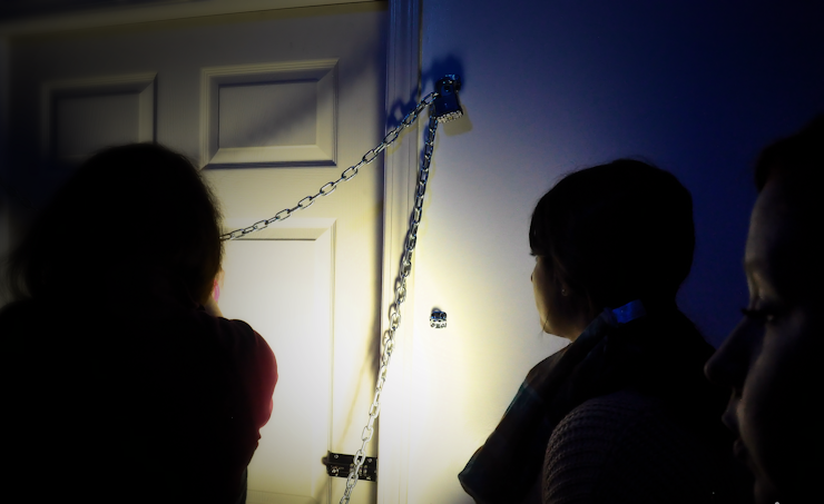 In-game: A team ini a dark room interacting with a door that is chained shut.