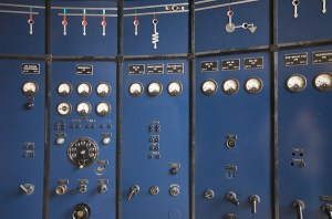 A beautiful old blue control panel with many small switches and gauges.