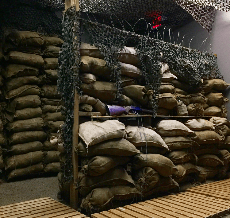 In game - A wall of sandbags and barbed wire with a rifle.