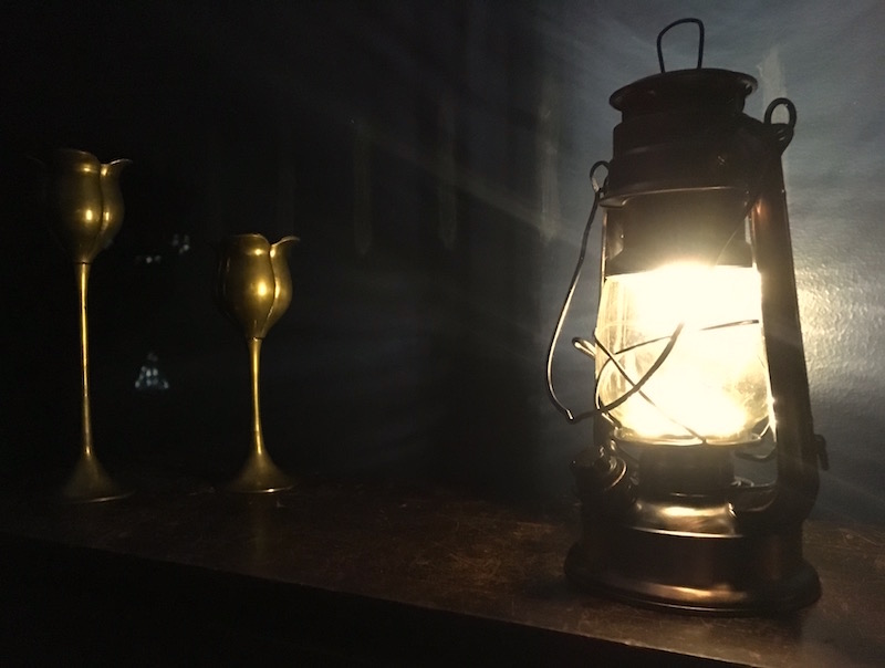 In-game: a glowing lantern upon a shelf illuminating a pair of goblets.