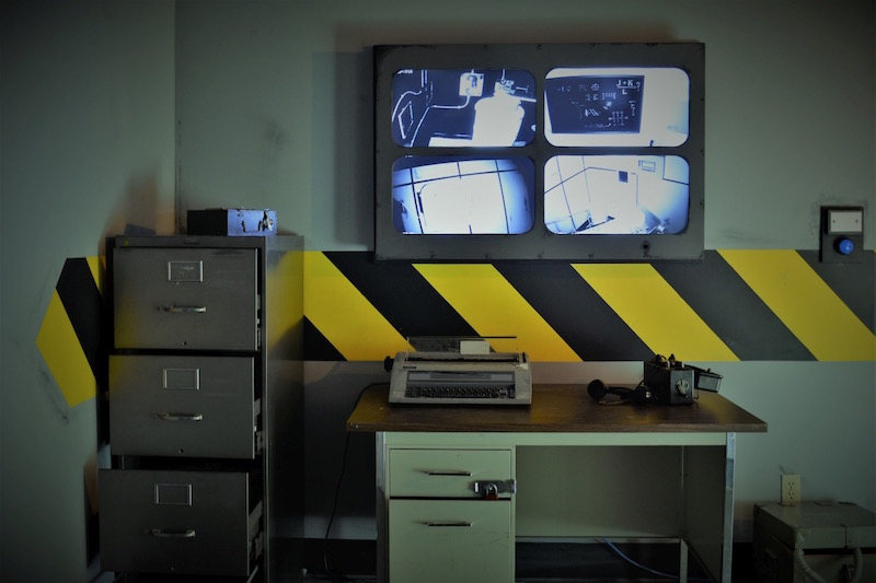 In game image at The Locked Room. A security office with camera screens, a desk with a typewriter, and a filing cabinet.