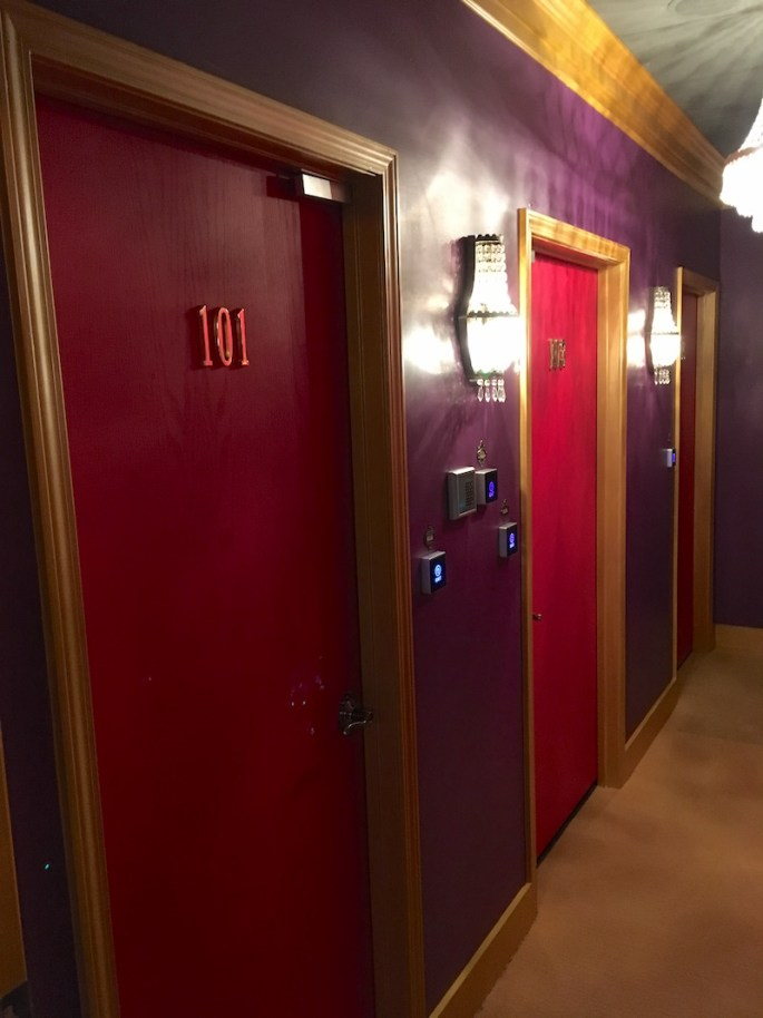 In-game: A hallway of hotel room doors.