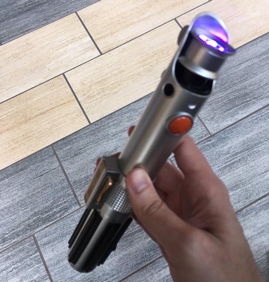 A hand holding a lightsaber that is glowing with UV light.