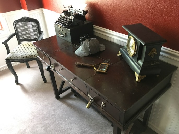In-game: An antique desk with an old magnifying glass, typewriter, clock, and a Sherlock Holmes double brim hat.